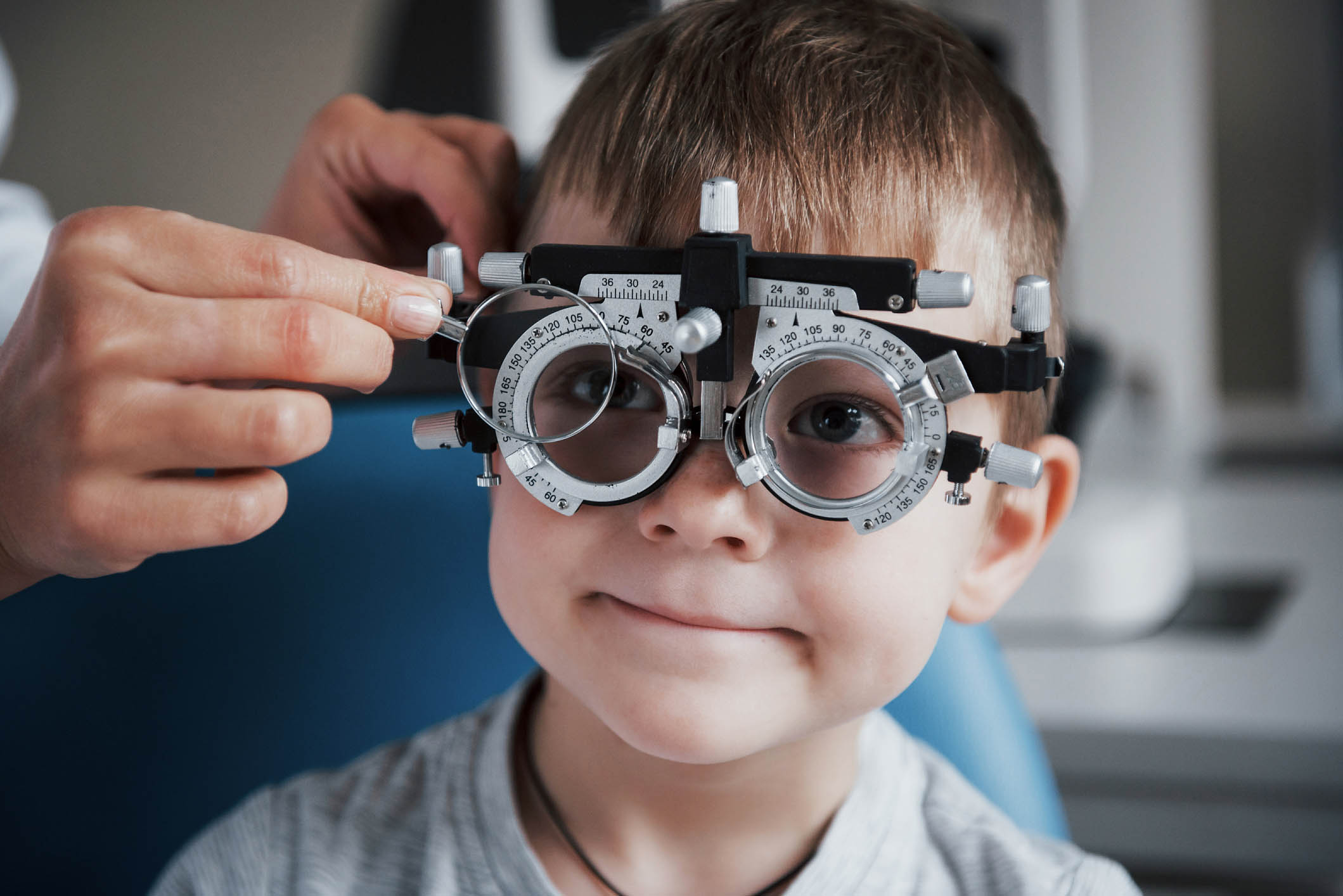 Tuning the intrument. Little boy with phoropter having testing his eyes in the doctor's office
