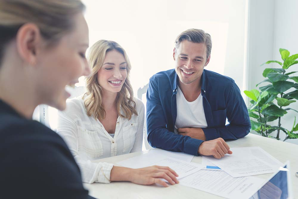 Insurance agent with couple looking through documents.